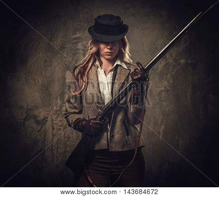 Lady with shotgun from wild west on dark background.