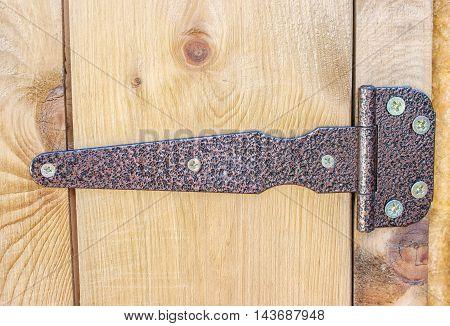 metal brown hinge on a wooden door closeup