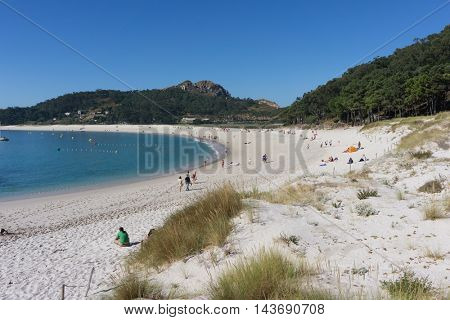 VIGO, SPAIN - AUGUST 18, 2016: Tourist on Rodas Beach on Cies Islands Natural Park off the coast of Vigo. With fine, white sand and clear waters, Rodas Beach is half a mile long and 200 feet wide.