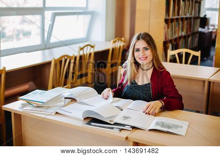 Smiling attractive female student sitting at desk in old university library preparing for exam and reading books. Education process.