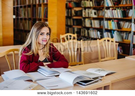 Female student with the books in old university library preparing for exam. Education concept