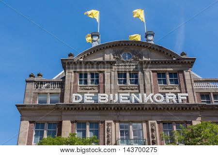Amsterdam the Netherlands - August 16 2016: The majestic facade of the luxury department store named De Bijenkorf. Yellow flags. Name prominently displayed in white on brown wall.