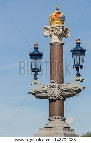 Amsterdam the Netherlands - August 16 2016: One of the decorative pillars and light poles on the Blauwbrug over the Amstel River is topped off by a golden crown.