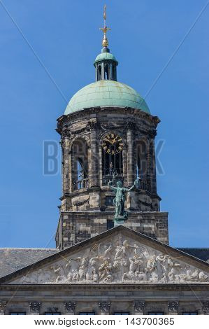 Amsterdam the Netherlands - August 16 2016: The top of the Royal Palace on the Dam against blue sky. Cut off at triangle mural. Statue niche and clock.