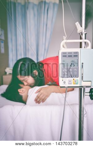 Illness asian child lying on sickbed with infusion pump intravenous IV drip. Mother take care her son. Shallow depth of field IV machine in focus. Health care and medical concept. Vintage tone effect.