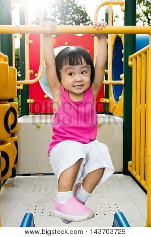 Asian Little Chinese Girl Hanging On Horizontal Monkey Bar