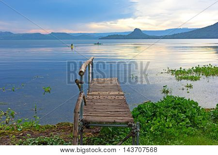 Fishermen boats on the lake Taal at sunrise Philippines. Lake Taal panorama with mountains on horizon.