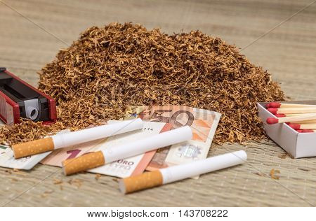 Handful of smoking tobacco surrounded by a cigarette manufacturing accessories