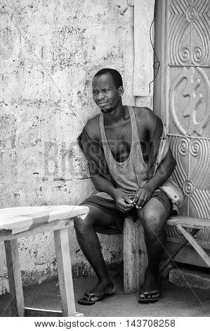 KARA, TOGO - MAR 9, 2013: Unidentified Togolese man sits on a bench. People in Togo suffer of poverty due to the unstable econimic situation