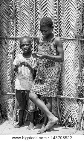 KARA, TOGO - MAR 9, 2013: Unidentified Togolese boy and girl stay in the street. Children in Togo suffer of poverty due to the unstable econimic situation