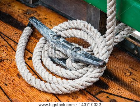 Close up mariner's rope wrapped around the cleat of a classic wooden boat