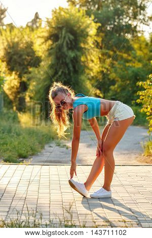 Young slim woman doing stretching back to the city park. Outdoors Sports. Healthy lifestyle concept. Morning exercises