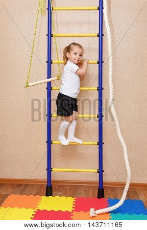 Little girl climbs the stairs. Wall bars. Sports Equipment. Children's sports.