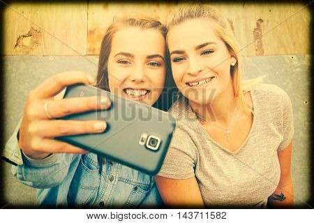 Two pretty girls taking selfie photo with phone camera