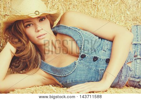 Beautiful cowgirl wearing denim and hat