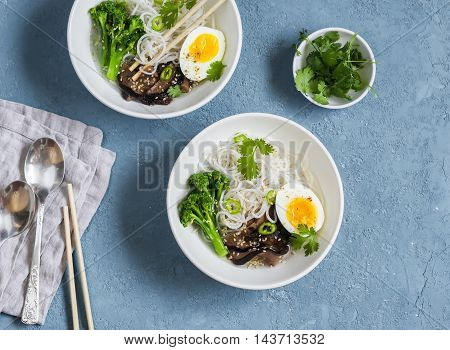 Rice noodles soup with broccoli mushrooms and boiled egg. Healthy vegetarian food top view