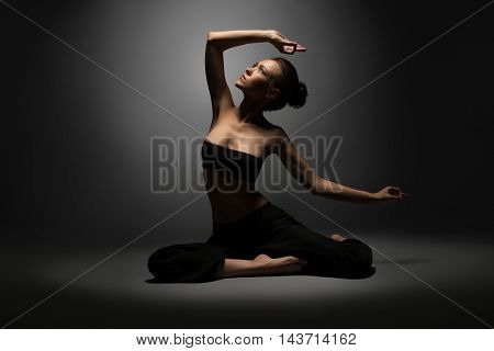 Studio photo of beautiful sexy girl doing yoga, on gray backdrop