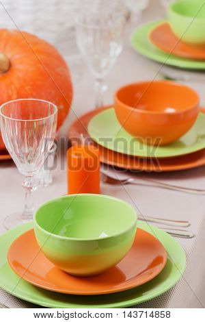 Thanksgiving Day. Festive lunch with traditional table decoration - pumpkins fruits and vegetables. Table setting in orange and green colors.