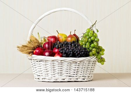 White basket with grapes apples and pears.