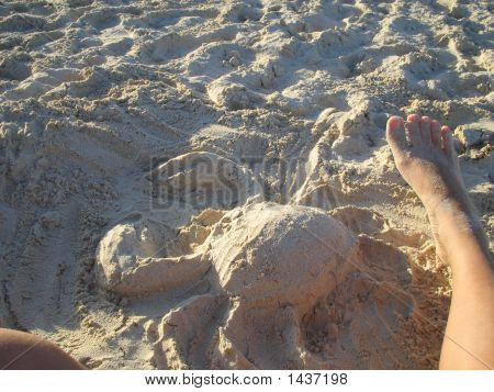 Sand Sculpture And Relaxing Feet On Beach