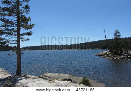 Tree and two rocky shores of pristine Lake Alpine, Highway 4, Sierra Nevada Mountains, California
