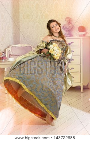 Pretty woman in luxury vintage dress standing in bright room