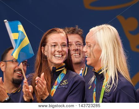 STOCKHOLM SWEDEN - AUG 21 2016: Swedish soccer player Lotta Schelin winning olympic silver waving the swedish flag when the swedish olympic athletes are celebrated in Kungstradgarden Stockholm Sweden August 21 2016