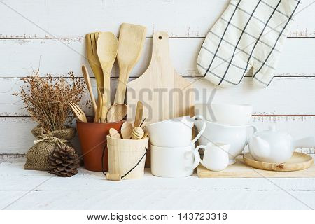 Kitchen cooking utensils on a shelf with white rustic wooden background