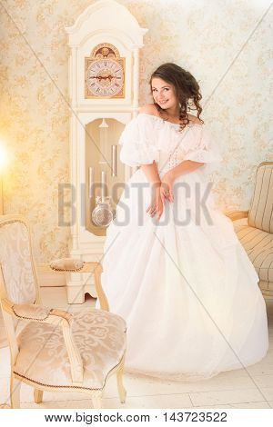 Pretty adult woman wearing vintage beautiful white dress standing in bright retro room