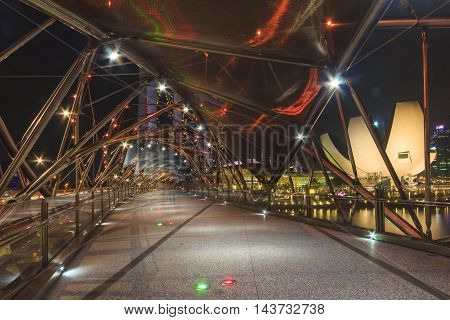 SINGAPORE SINGAPORE - SEPTEMBER 28 2013 : Night view of Helix bridge which leading to Marina Bay Sands luxury hotel a famous tourist attraction of Singapore.