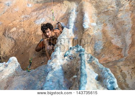 Top View of Rock Climber on orange Vertical Wall naked Torso looking up