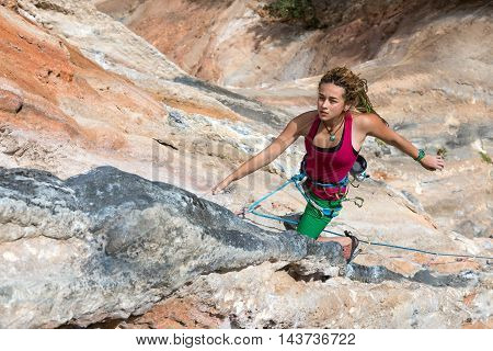 Portrait of Cute Girl rock Climber hanging on vertical orange wall energetic passionate Face Expression elegant Pose looking up orange and blue colour Stone Formations