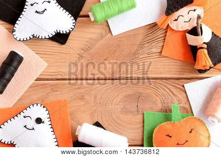 Halloween felt craft embellishments. Hand made witch with broom, pumpkin head, two ghosts. Mixed Halloween ornaments, colored felt sheets on wooden table with copy space for text. Fall background