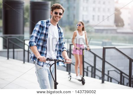 Rest with pleasure. Cheerful handsome smiling man riding a kick scooter and expressing joy with his friend