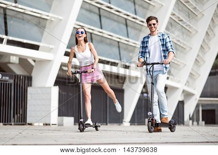 Active way of life. Cheerful delighted smiling friends riding kick scooters while resting together outdoors