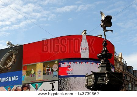 LONDON ENGLAND - JULY 8 2016: Piccadilly Circus neon signage and the Statue of Eros on top of the Shaftesbury Memorial a famous public space in West End.
