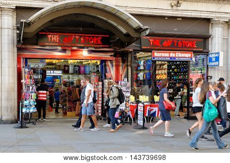 LONDON ENGLAND - JULY 8 2016: People walk past a popular souvenirs shop on Piccadilly circus. This is one of the main tourist attractions visited by millions of tourists.