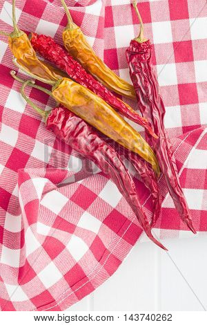 Dried chili peppers on checkered napkin.