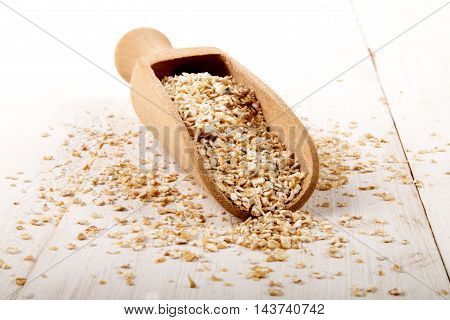 raw oat bran and wooden scoop on white wood