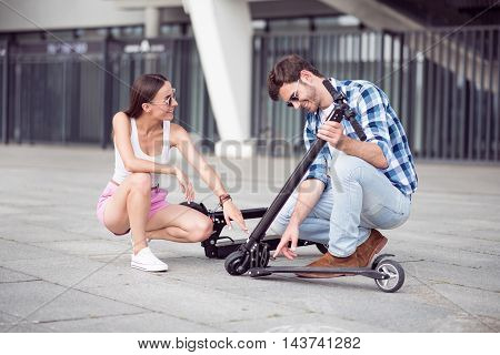 Share true emotions. Cheerful content friends sitting near kick scooter and smiling while resting