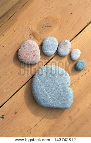 Stone Pebbles composed as human foot trace on natural wooden floor