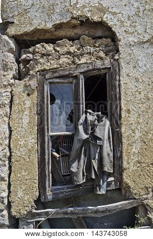 Old window on a semi collapsed rural home with jacket