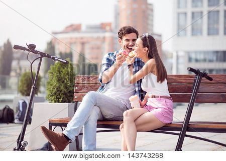 Sweeten your life. Positive content loving smiling couple eating doughnuts and relaxing while sitting on the bench