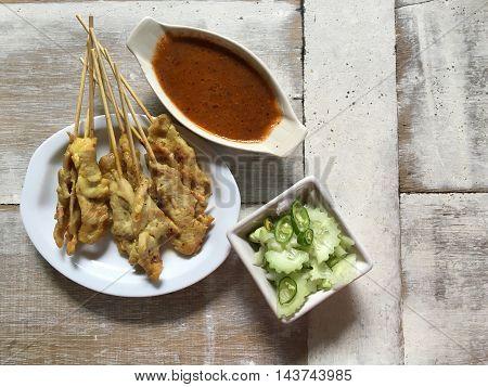 Pork satay dish on a wooden table .