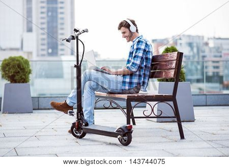 In a good mood. Positive content smiling man sitting on the bench and using laptop while resting