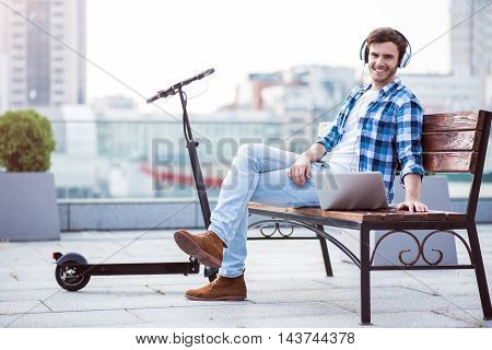 True emotions. Cheerful handsome smiling man listening to music and using laptop while sitting on the bench