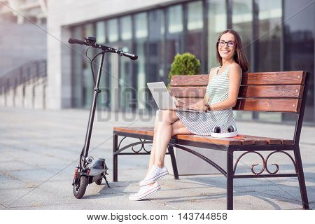 In touch with the world. Positive delighted woman smiling and using laptop while sitting on the bench