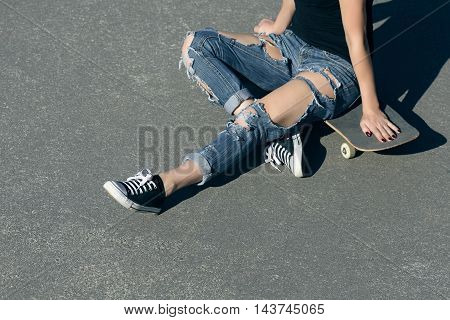 young woman sitting on a skateboard in torn jeans