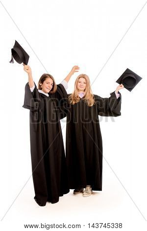 Full length portrait of two joyful graduating students. Isolated over white background.