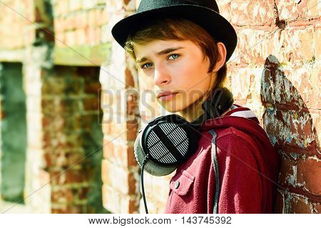 Teenage boy with headphones leaning to a brick wall on the street. Modern generation. Summer holidays.